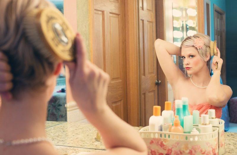 Блондинка за косметическим столиком наносить макияж