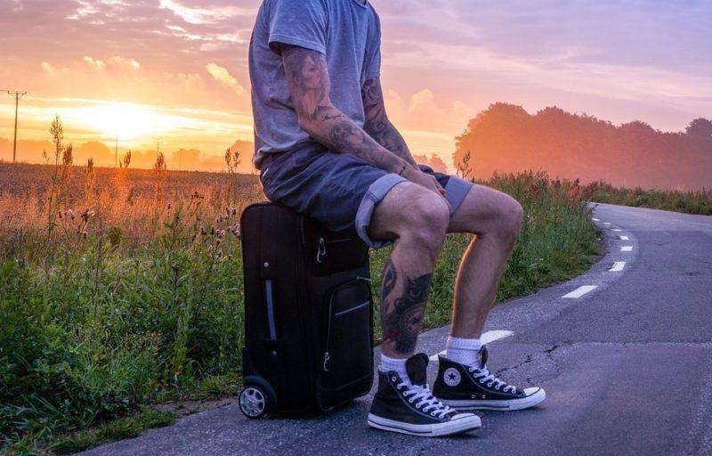 Парень с тату на ногах и руках сидит на чемодане