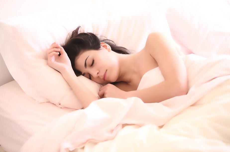 Девушка спит в белой кровати